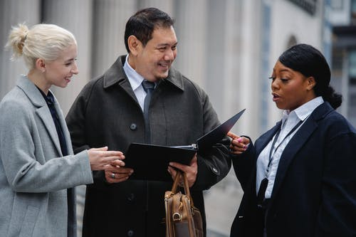 Smiling multiracial coworkers wearing formal outfits standing on street with paper folder and discussing business project together
