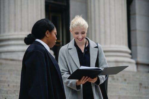 性格開朗的多民族女同事在大街上閱讀文檔