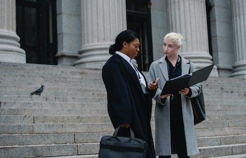 Smart diverse businesswomen reading documents on street near columned building