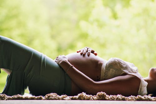 Side view of peaceful woman in expectancy touching belly while resting on wooden balcony against greenery