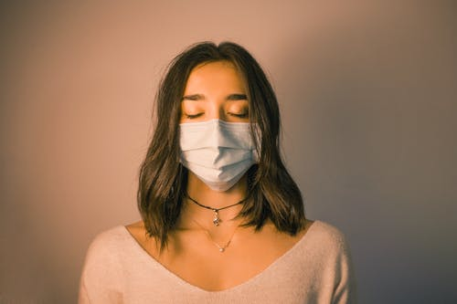 Calm woman in face mask standing against dark pink wall