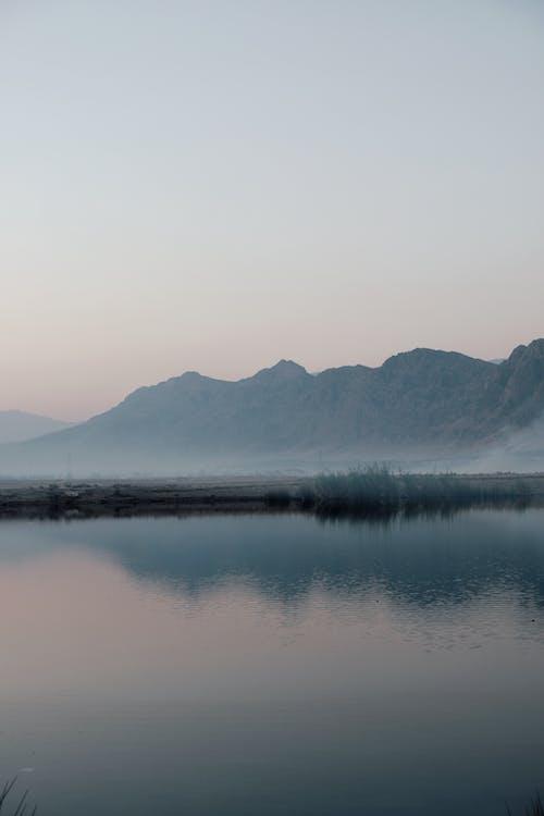 Lake Near Mountain Under Gray Sky