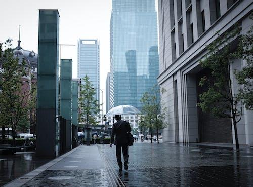 Person in Black Jacket Walking on Sidewalk