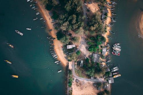 Boats floating near sandy coastline