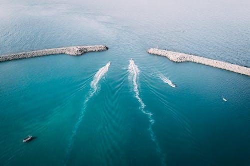 Ships sailing through sea and leaving ships wakes between breakwaters