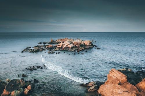Dark blue sky over boulders in sea near coast