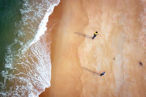 Top view of unrecognizable travelers walking on sandy shore of green wavy ocean in sunlight