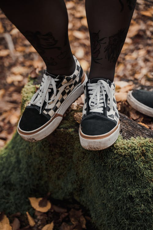 Crop anonymous female with tattoos in sneakers standing on log with moss in autumn park