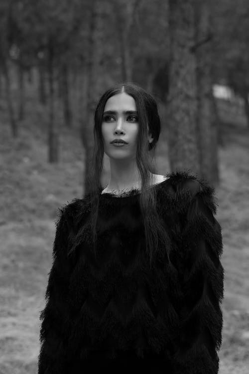 Black and white unemotional young female in black sweater standing in woodland calmly and looking away