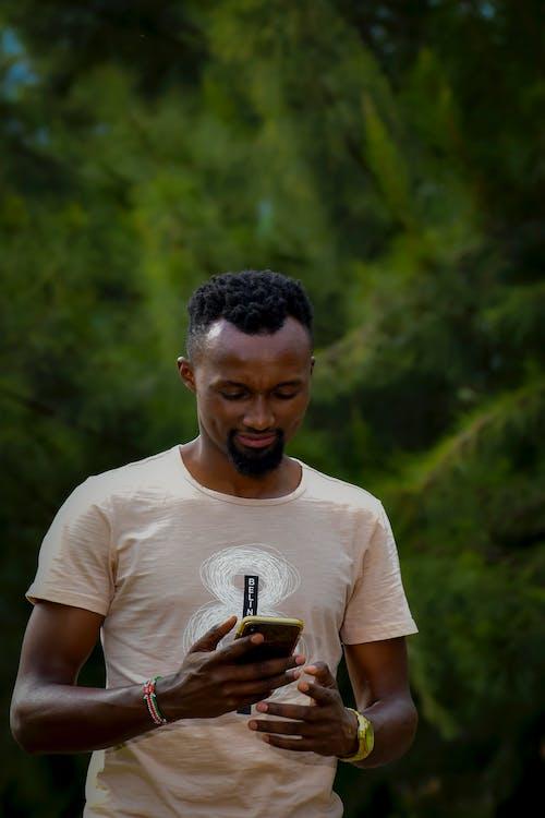 Man in White Crew Neck T-shirt Holding Black Smartphone