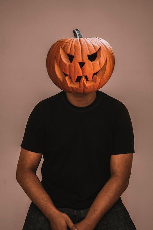 Man in Black Crew Neck T-shirt With Jack O Lantern on Head