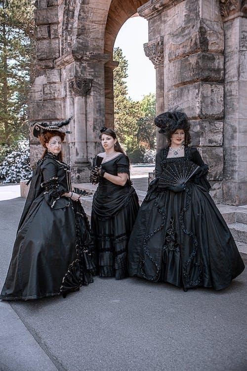 2 Women in Black Dress Standing on Gray Concrete Floor
