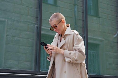 Cheerful stylish woman using smartphone on street