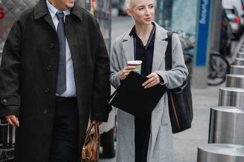 Crop happy young female entrepreneur in elegant coat holding paper folder and cup of takeaway coffee while walking on street with unrecognizable male colleague during break