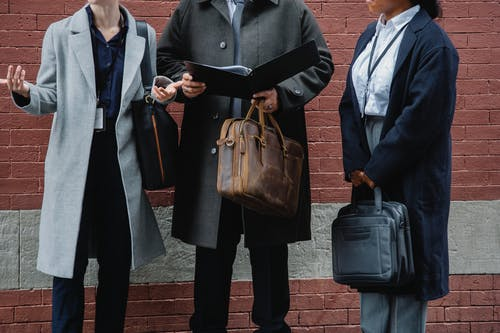 Faceless multiethnic colleagues sharing documents on street near brick building