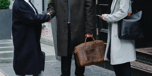 Crop anonymous trendy businessman and businesswomen in elegant outerwear shaking hands on street