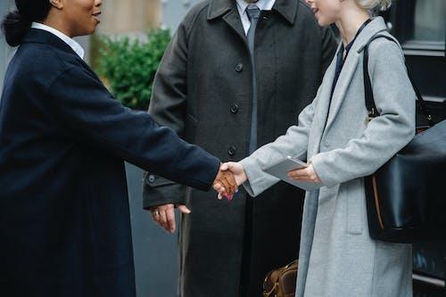 Multiracial women in stylish coats shaking hands near man