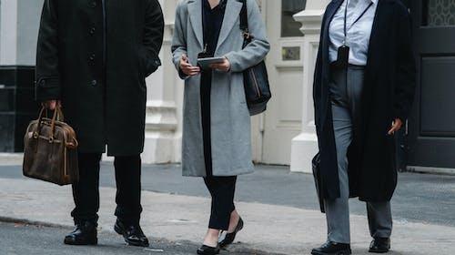 Stylish businesspeople in elegant coats walking on street