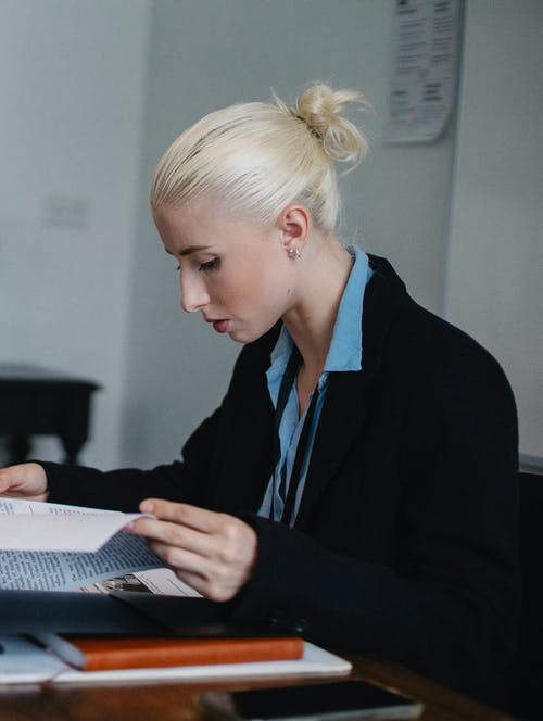 Content serious businesswoman reading important report in office
