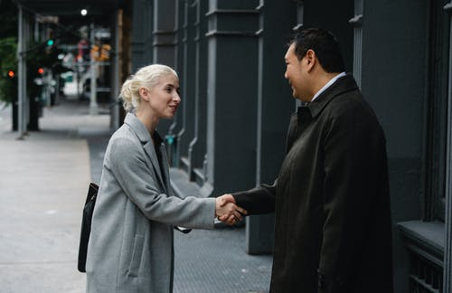Young businesswoman shaking hands with Asian colleague