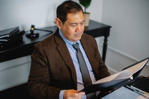 Pensive Asian lawyer examining report in office