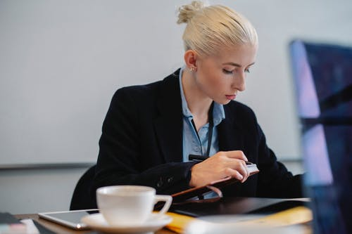 Serious young businesswoman working with report in office