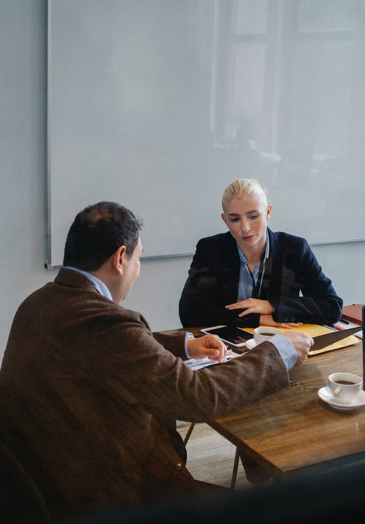 Smart colleagues in formal outfit discussing business while sitting at table with cups of coffee in office with whiteboard