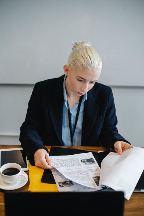 Serious businesswoman checking papers at table with cup of coffee