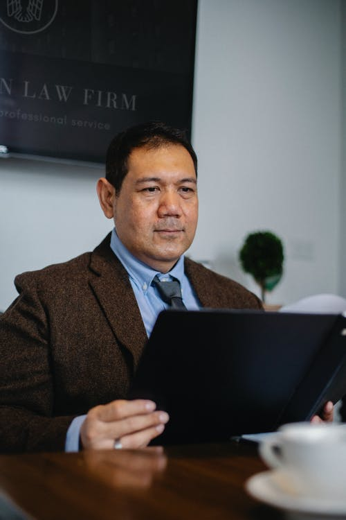 Mature ethnic experienced lawyer in elegant outfit watching important report in folder in office