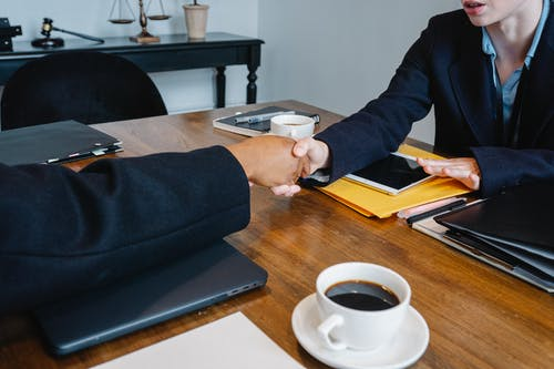 Diverse anonymous colleagues shaking hands at table with coffee and folders