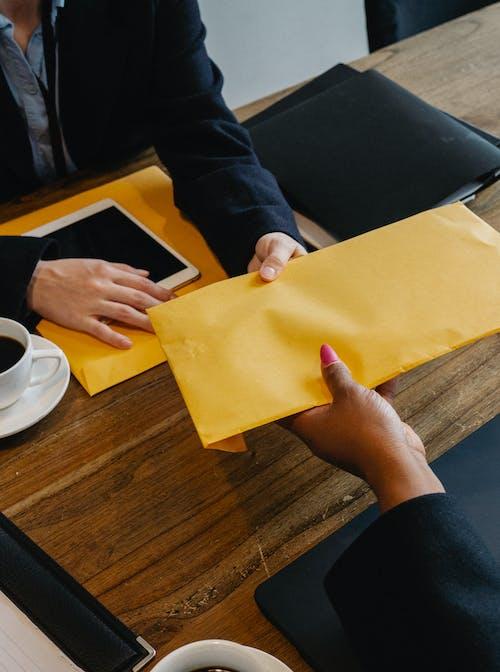 Businessman giving bright envelope to black businesswoman