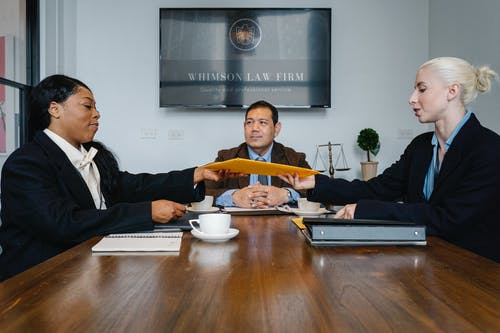 Black judge giving yellow envelope to young businesswoman