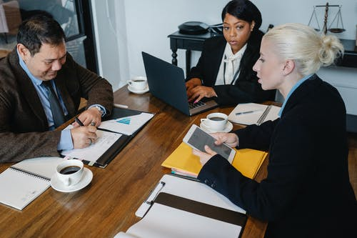 Diverse businesspeople discussing documents at table in office