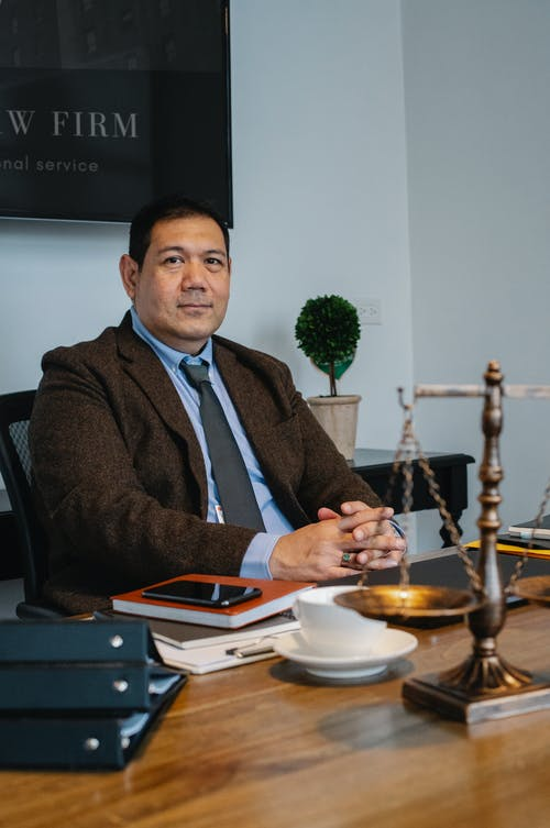 Middle aged ethnic legislator looking at camera and sitting at table with scales of justice in office