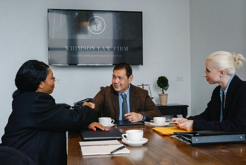 Многонациональные коллеги пожимают друг другу руки в адвокатском бюро