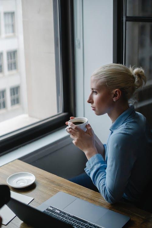 Businesswoman drinking coffee in modern office