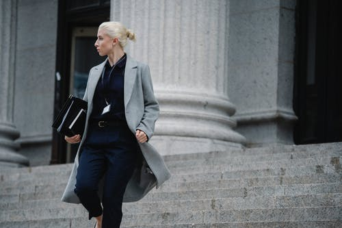 Serious female lawyer in elegant outfit holding folders with documents while going downstairs near stone state building and looking away