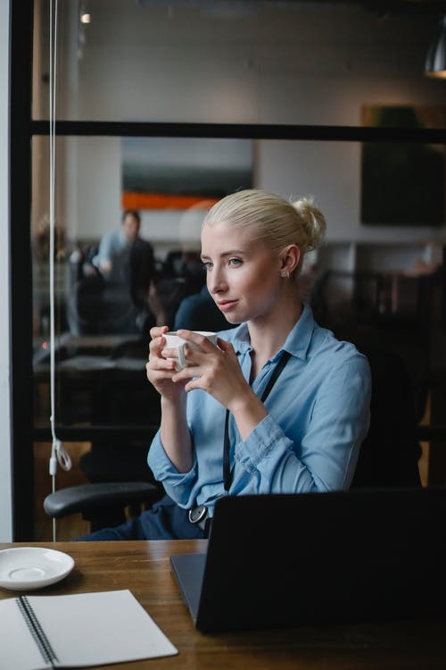 Young female manager in formal wear sitting at table with laptop and notepad while holding cup of hot drink and looking away