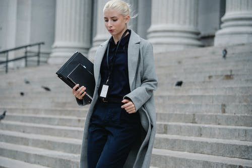 Serious businesswoman hurrying with documents from courthouse