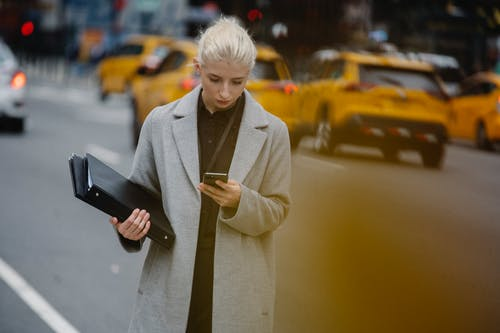 Young attentive female executive surfing internet on cellphone while standing with folders on city roadway