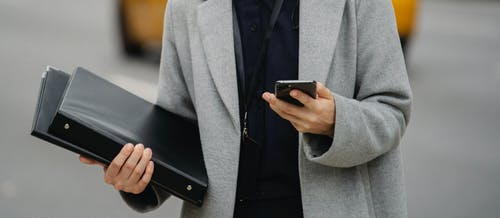 Crop anonymous well dressed female executive with folders text messaging on cellphone on urban road
