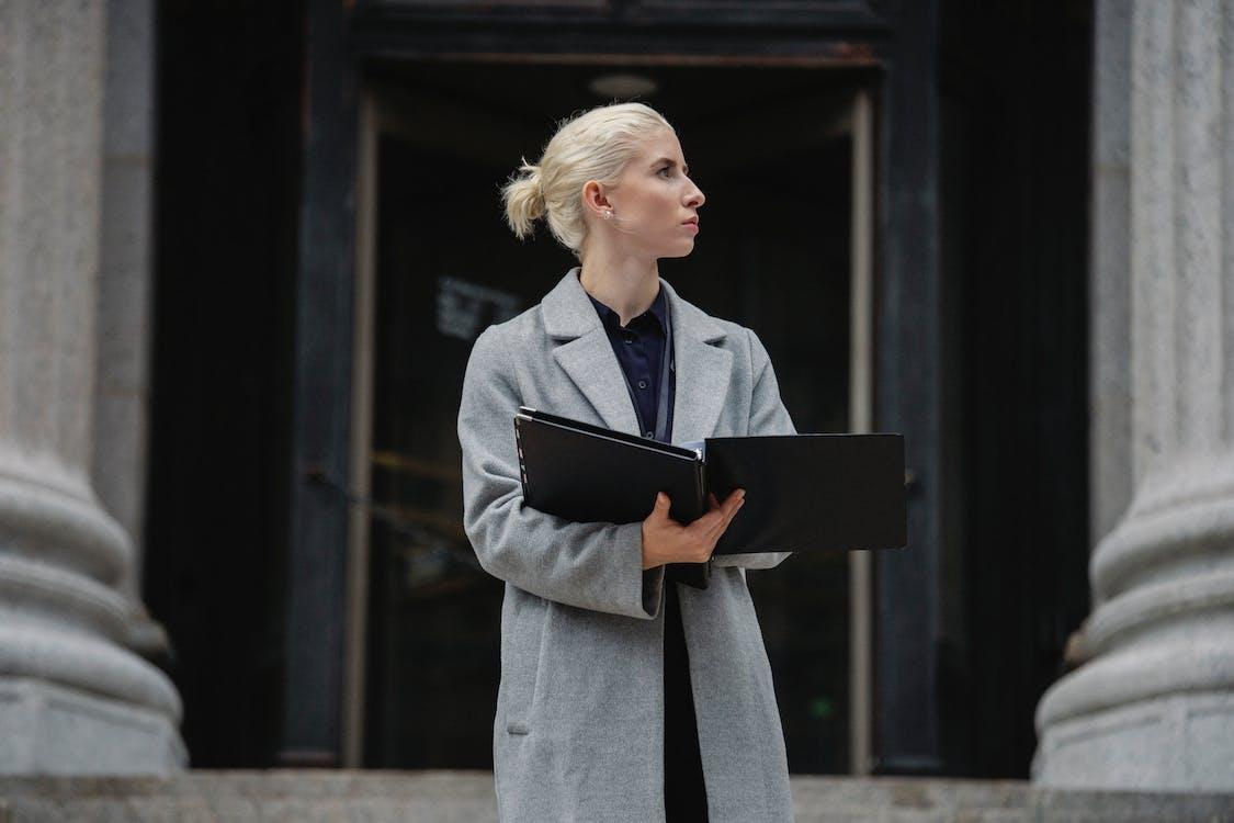 внимательная женщина руководитель с папками против городского строительства