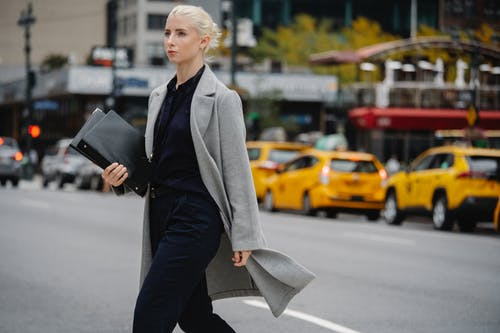 Young confident well dressed blond female entrepreneur with folders walking on asphalt roadway while looking forward in town