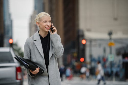 Young smiling blond female manager with folders speaking on cellphone on urban road while looking forward