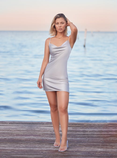 Woman in White Spaghetti Strap Dress Standing on Wooden Dock