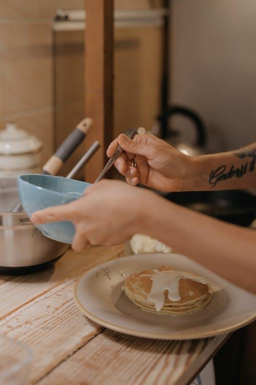 Person Preparing Pancakes for Breakfast
