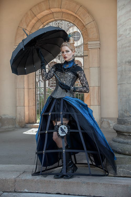 Woman in Blue and Black Dress Holding Umbrella