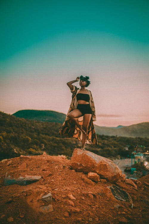 Black woman standing on rock in hilly valley