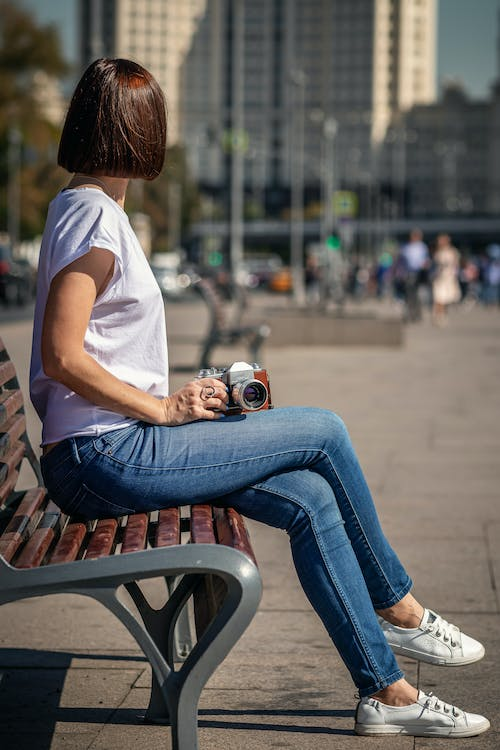 Woman in White T-shirt and Blue Denim Jeans Sitting on Brown Wooden Bench Holding White