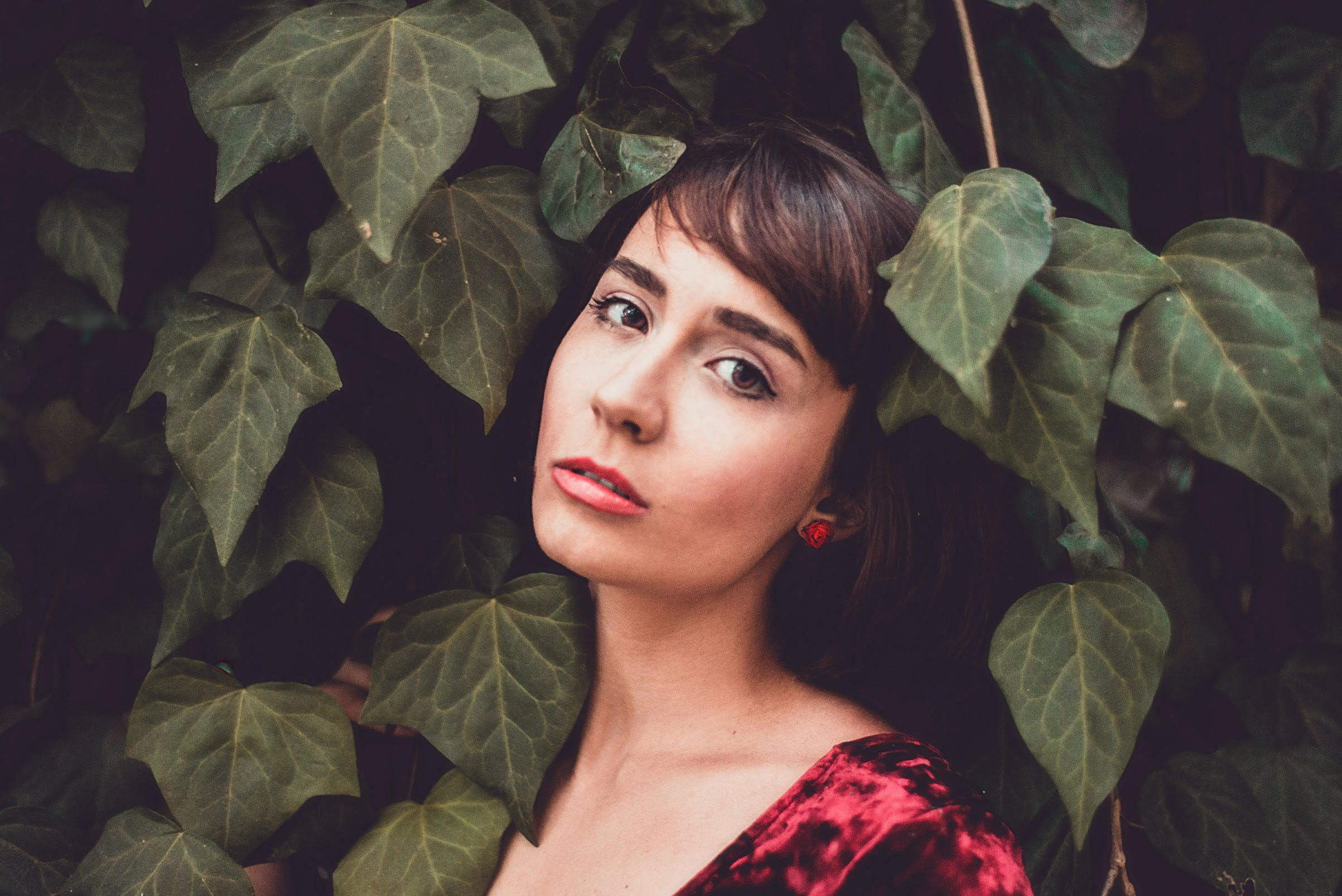 Woman Wearing Red Top Behind Green Leafed Plants